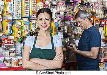 verkäuferin, mit, verschränkte arme, stehende , während, kunde, auswählen, p