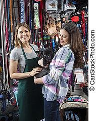 verkäuferin, stehende , mit, weibliche , kunde, tragen, französische bulldogge