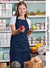 verkoopster, appeltjes , supermarkt, vasthouden