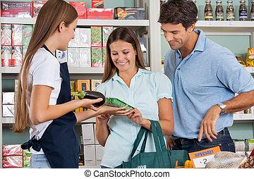verkoopster, helpen, paar, in, aankoop, kruidenierswaren