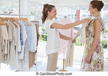 verkoopster, helpen, vrouw, met, kleren, op, de opslag van...