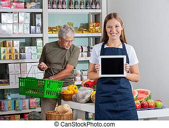 verkoopster, het tonen, digitaal tablet, terwijl, hogere mens, shoppen
