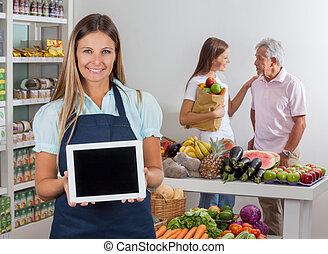 verkoopster, het tonen, tablet, met, klanten, in, achtergrond