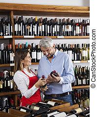 verkoopster, het tonen, wijn bottelt, om te, klant, in, supermarkt