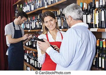 verkoopster, het tonen, wijn fles, om te, klant, in, supermarkt