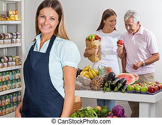 verkoopster, met, familie winkelen, in, achtergrond