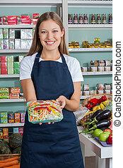 verkoopster, vasthouden, groente, pakket, in, grocery slaan op