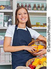 verkoopster, vasthouden, plantaardige mand, in, grocery slaan op