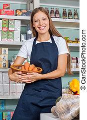 verkoopster, vasthouden, plantaardige mand, in, supermarkt