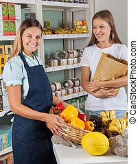 verkoopster, vasthouden, plantaardige mand, met, vrouwlijk, klant