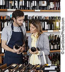 verkoper, het bespreken, op, wijn bottelt, met, klant