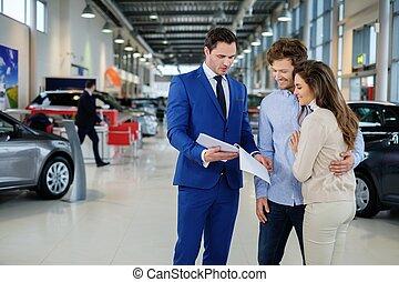 verkoper, sprekend aan, een, jong paar, op, de, dealership,...