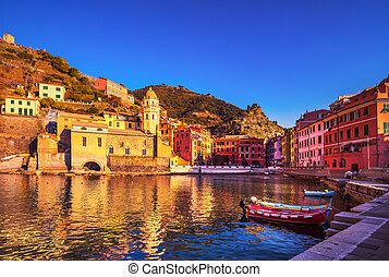 Vernazza village, church, boats and sea harbor on sunset. Cinque Terre, Ligury, Italy