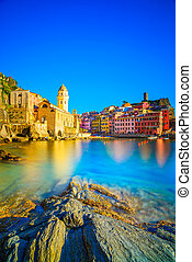 Vernazza village, church, rocks and sea harbor on sunset,...