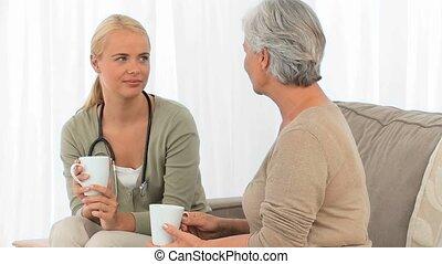 verpleegkundige, hebben, een, kop van thee, met, haar, patiënt