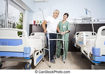 verpleegkundige, helpen, mannelijke , patiënt, in, gebruik, walker, op, rehab, centrum