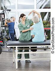 verpleegkundige, helpen, oude vrouw, in, arm, oefening, in, rehab, centrum