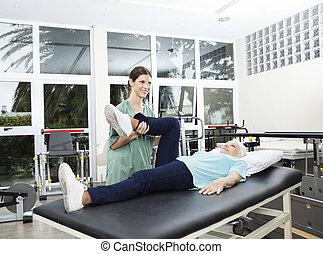 verpleegkundige, helpen, oude vrouw, in, been, oefening, op, rehab, centrum