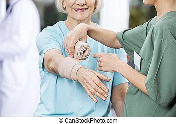 verpleegkundige, het putten, gummi verband, op, patiënt, hand, op, rehab, centrum