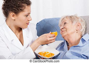 verpleegkundige, het voeden, oudere vrouw