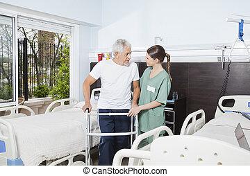 verpleegkundige, portie, mannelijke , patiënt, in, gebruik, walker, op, verpleeghuis
