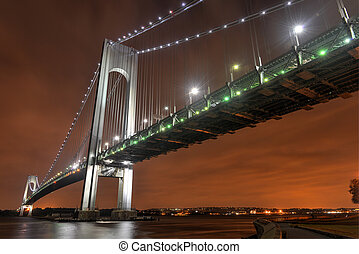 Verrazano Narrows Bridge at night from Brooklyn. The bridge a double-decked suspension bridge that connects the boroughs of Staten Island and Brooklyn in New York City at the Narrows.