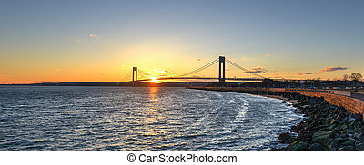 Verrazano Narrows Bridge At Sunset from Brooklyn. The bridge a double-decked suspension bridge that connects the boroughs of Staten Island and Brooklyn in New York City at the Narrows.