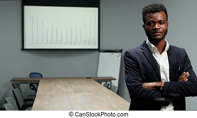 verticaal, van, afrikaanse amerikaan, zakenman, in, kostuum, en, wit hemd, staand, in, de werkkring, op, de, achtergrond, van, een, groot, tafel, en, diagrammen, op, de, scherm, kijken naar van het fototoestel
