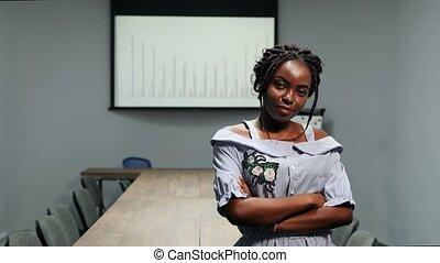verticaal, van, afrikaanse amerikaan, zakenman, staande vrouw, in, kantoor, voor, een, groot, tafel, en, grafieken, op, de, scherm, kijken naar van het fototoestel