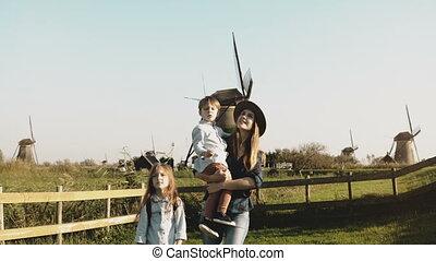 verticaal, van, een, europeaan, gezin, dichtbij, windmolen, farm., mooie vrouw, in, hoedje, met, jongetje, en, meisje, wandeling, samen., 4k.