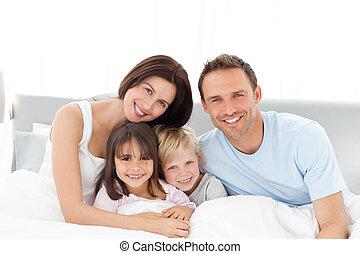 verticaal, van, een, gelukkige familie, zitting op het bed