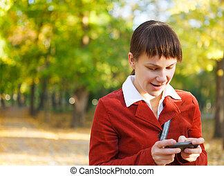 verticaal, van, een, het glimlachen, mooie vrouw, texting, met, haar, telefoon