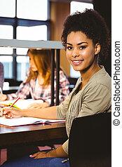 verticaal, van, een, het glimlachen, student, zitting op het bureau, kijken naar van fototoestel
