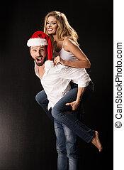 verticaal, van, een, jong paar, met, kerstmuts, het kijken in de camera