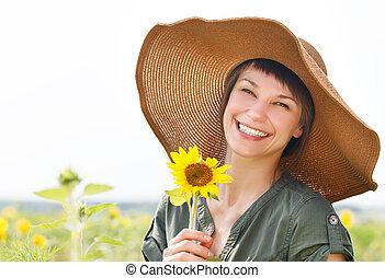 verticaal, van, een, jonge, glimlachende vrouw, met, zonnebloem