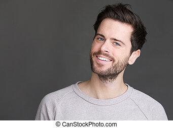 verticaal, van, een, jonge man, het glimlachen, op, vrijstaand, grijze achtergrond