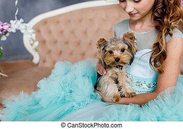 verticaal, van, een, mooi, jong meisje, met, blauwe ogen, opmaken, en, hairstyle, in, sterke drank, turkoois, jurkje, met, yorkshire terrier