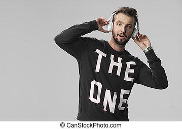 verticaal, van, een, mooi, jonge man, het luisteren, muziek, tegen, een, grijze , achtergrond
