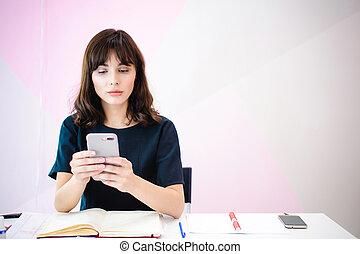 verticaal, van, een, mooi, zakenmens , vervaardiging opmerkingen, in, een, smartphone., vasthouden, een, mobiele telefoon, terwijl, zittende , in, een, werkplaats, in, een, roze, kantoor