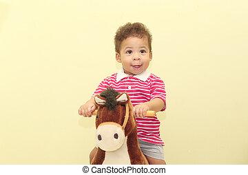 verticaal, van, een, schattige, afrikaan, jongen, in, zijn, paarde, toy.