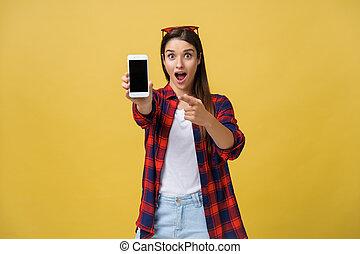 verticaal, van, een, verwonderd, vrouw, in, ongedwongen, doek, het tonen, blank lichten door, mobiele telefoon, vrijstaand, op, gele achtergrond