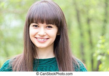 verticaal, van, jonge, mooie vrouw, brunette, meisje, gelukkig glimlachen, &, kijken naar van fototoestel, op, zomer, groene, buitenshuis, achtergrond