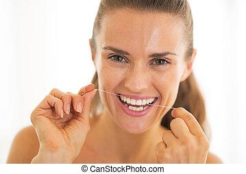 verticaal, van, jonge vrouw , gebruik, dentale floss