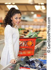 verticaal, van, jonge vrouw , met, boodschappenmand, staand, op, checkout logenstrafen, in, supermarkt