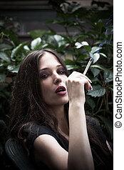 verticaal, van, jonge vrouw , met, sigaret, in, tuin