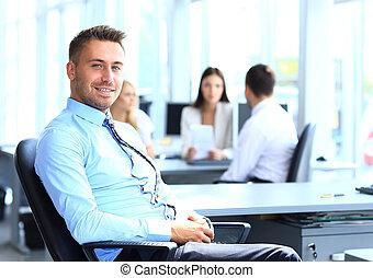 verticaal, van, jonge, zakenman, in, kantoor, met, collega's, in, de, achtergrond