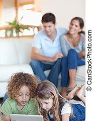 verticaal, van, kinderen, gebruik, een, tablet, computer, terwijl, hun, ouders, zijn, schouwend, in, hun, woonkamer