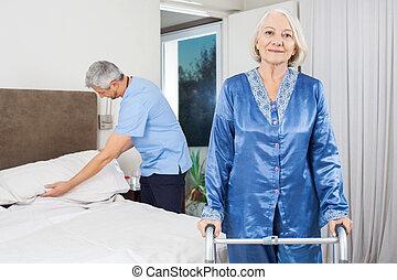 verticaal, van, oude vrouw, met, lopend met vensterraam, op, verpleeghuis