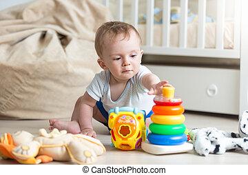 verticaal, van, schattige, toddler, jongen, spelend, met, kleurrijke, speelbal, piramide