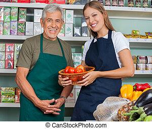 verticaal, van, verkoopster, vasthouden, plantaardige mand, met, mannelijke , collega, in, grocery slaan op